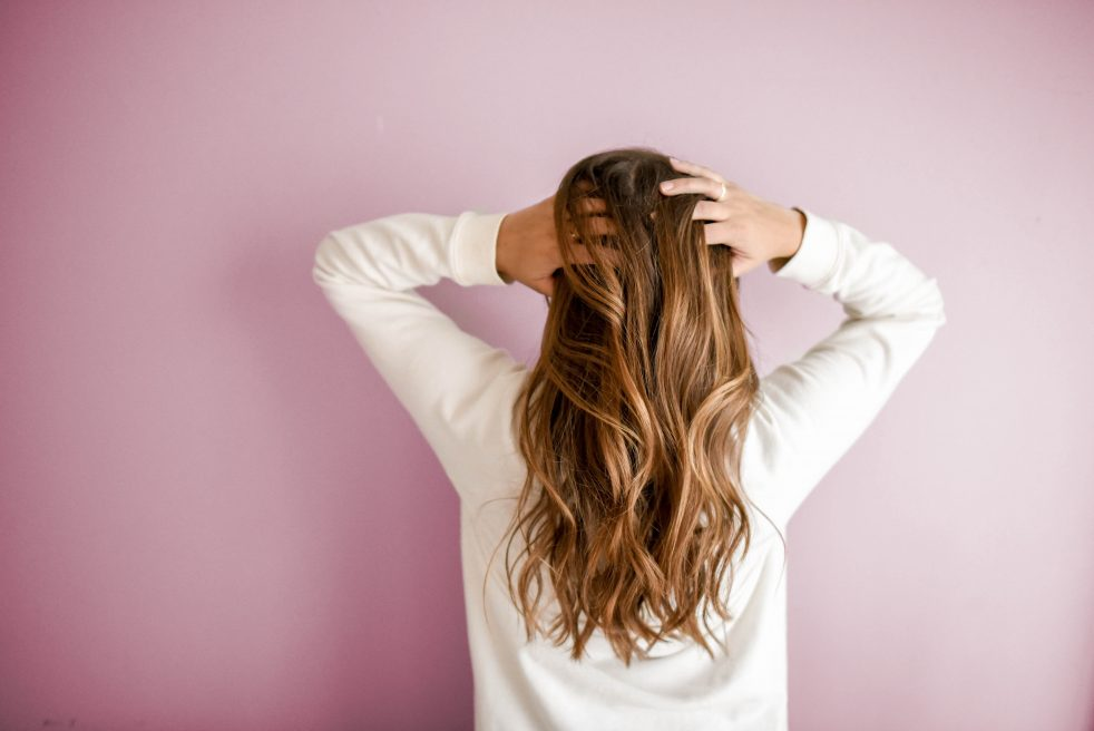 Woman standing with her hands in her hair, because she doesn't know where to go to grieve the loss of her child.