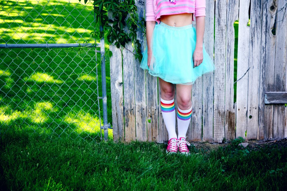 Image of a child wearing a pink top, blue skirt, and rainbow socks, for the purpose of the blog post wondering if you can tell if your child is lgbtq before they come out.