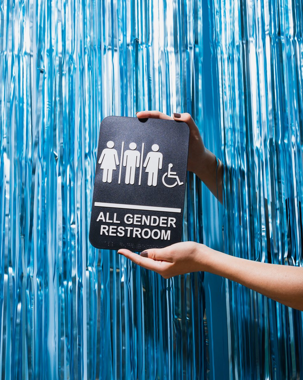 Gender-nuetral bathroom sign in front of blue background to support transgender people for TDOV.