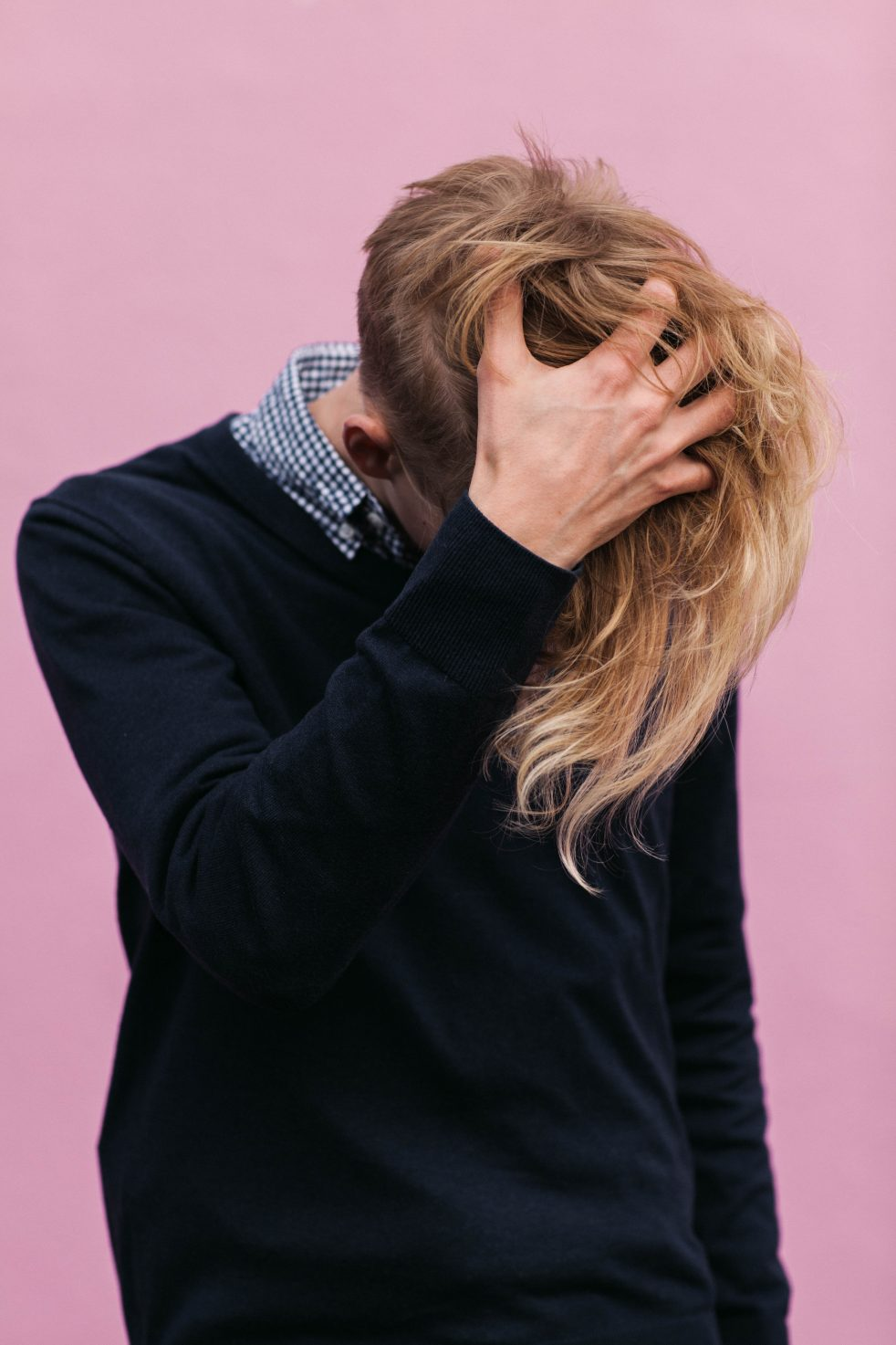 Image is a person with blonde hair, looking at the ground, their hand in their hair, wearing a dark blue sweater and light blue button shirt under it, against a dusty pink background.