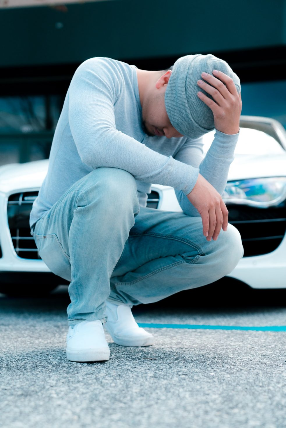 Image is of a man dressed in a light blue long-sleeve top, pants, and knit cap, squatting in front of a car with his head down and face hidden like he's sad about something. Sometimes your emotions just get the best of you and you need a minute to recover.