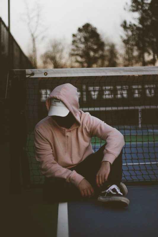 Man in pink hoody pulled up over a white ball cap, wearing black joggers sits on the ground. He is looking down to emphasize the fact that you shouldn't grieve in front of your child.