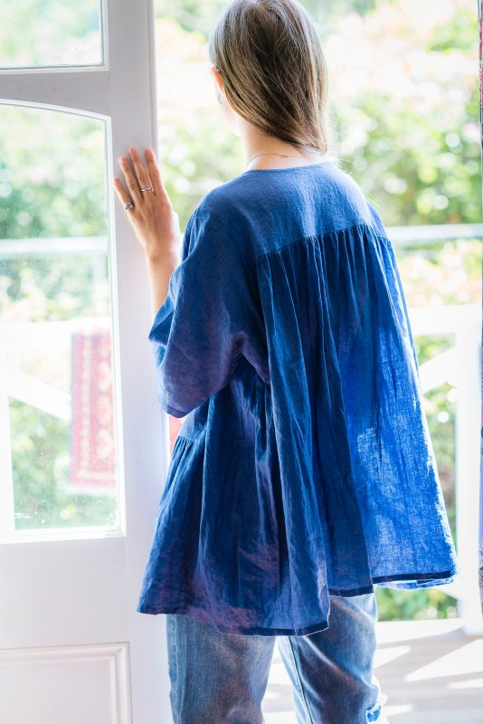 Woman in a blue shirt standing in front of a doorway looking out, to emphasize the fact that you shouldn't grieve in front of your child.
