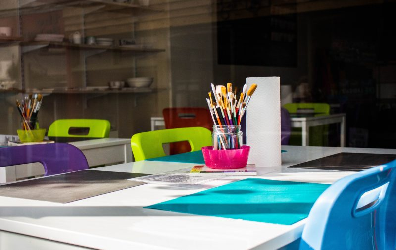 Image is a child's classroom with multicolored chairs around a table and a jar of paintbrushes in the middle. The image is for a post called do we tell our child's teacher they are transgender?