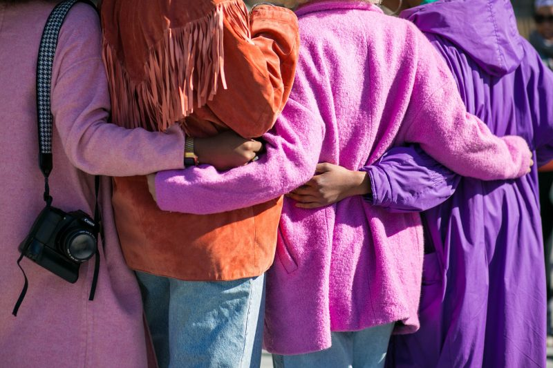 Image is four people wearing pink, orange, and purple coats, with their arms around each other. They support each other as they stand facing away from the camera.