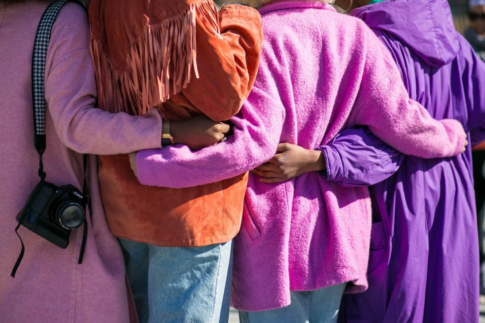 The image is four people wearing coats of purple, orange, and pink, standing facing away from the camera. They have their arms around each other's waists. They support each other as they sand there.