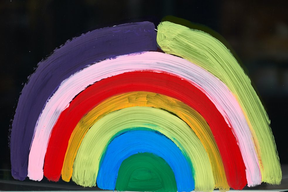 Photo is a painted rainbow in front of black background for a post about supporting parents with tips for national come out day.
